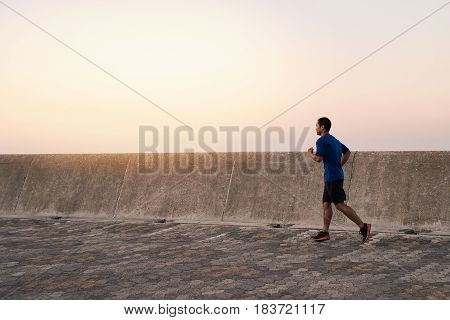Fit and focused young Asian man in sportswear running alone along a boardwalk outside in the early morning