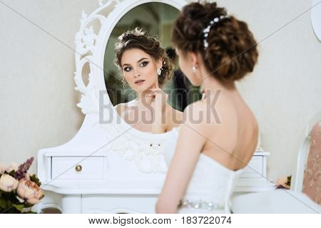 Beautiful young bride in front of the mirror. Portrait with wedding makeup hairstyle dress
