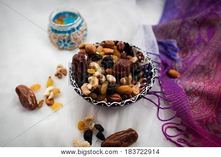 blue plate with nuts and dried fruits lying on a white table