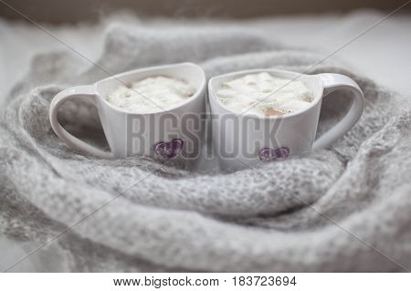 two white mugs with marshmallow on the background of the grey wool scarf