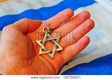 Hand holding a Jewish Star of David with Israel flag on the background. Hebrew kosher concept stock image. Israel Independence Day