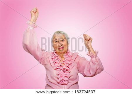 The portrait of a cheerful senior woman gesturing victory over pink background