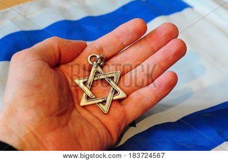 Hand holding a Jewish Star of David with Israel flag on the background. Israel Independence Day, Jewish, Hebrew concept illustration.
