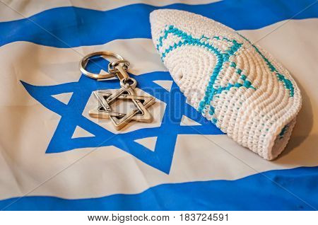 Folded Jewish customary kippah cap, a Star of David on the unfolded Flag of Israel. Judaism vs. Zionism. Israel Independence Day, Holocaust Remembrance abstract concept illustration.
