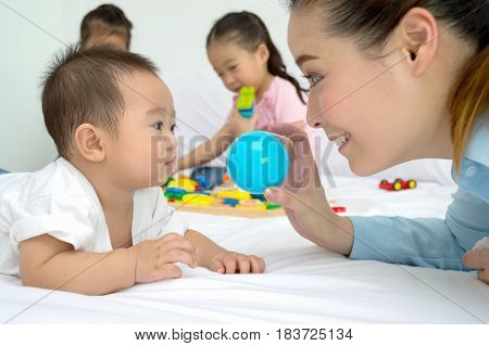 Mom is playing toys with her baby in the bedroom.