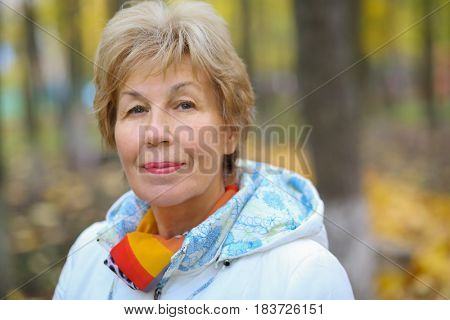 Elderly happy blonde woman looks at camera in autumn park, shallow dof