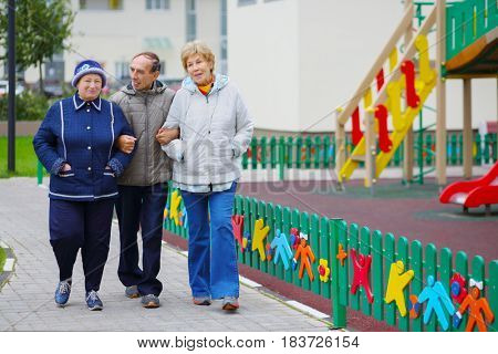 Two elderly women and man walk near playground near building at autumn day