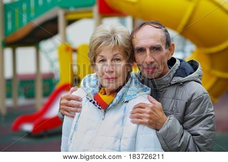 Elderly woman and man embrace on playground at autumn, shallow dof