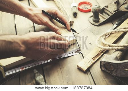 Artist canvas on man hand canvas stretcher and staple gun on table
