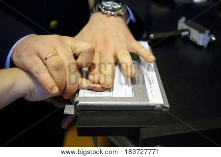 Hands of two men during fingerprinting, text translate - dactyloscopic registration, pinky