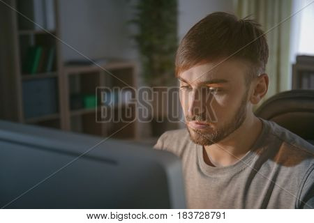 Young programmer at workplace in the evening