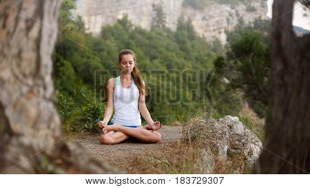 Young woman meditating outdoors, girl doing yoga high in the mountains, relaxation self-reflection healthy lifestyle concept