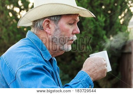 Senior in cowboy hat blowing steam from hot drink