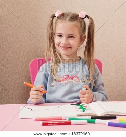 the beautiful happy girl drawing at home