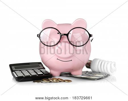 Cute pink piggy bank with glasses, money and bulb on white background