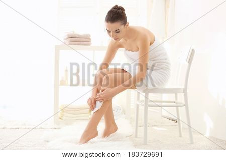 Young woman depilating legs with wax sitting on chair