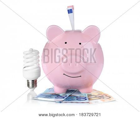 Cute pink piggy bank with money and bulb on white background