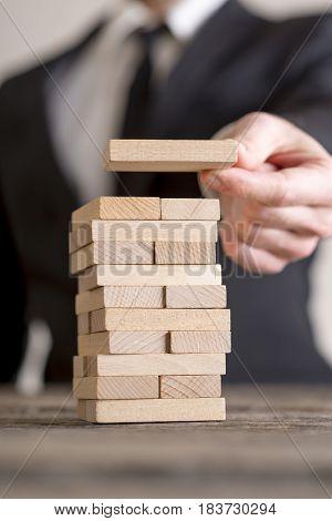 Businessman blurred in background stacking wooden bricks building business concept.