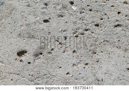 A piece of concrete wall with pebbles. Recesses in the concrete wall from the off . In concrete inclusions of small pebbles of gray and brown.
