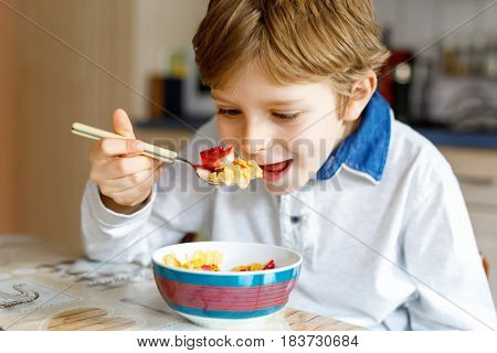 Adorable little blond school kid boy eating cereals with milk and berries, fresh strawberry for breakfast or lunch. Healthy eating for children, schoolkids. At school canteen or at home.