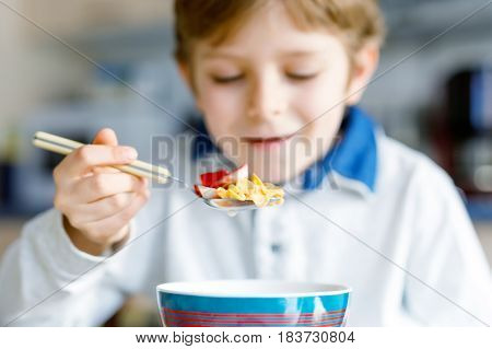little school kid boy eating cereals with milk and berries, fresh strawberry for breakfast or lunch. Healthy eating for children, schoolkids. At school canteen or at home. Selective focus