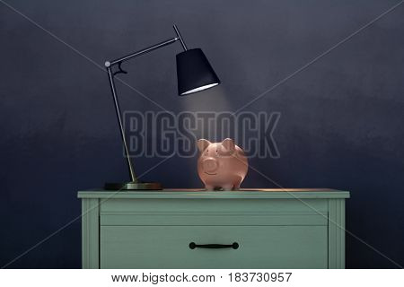 Table with cute piggy bank on illuminated surface under lamp