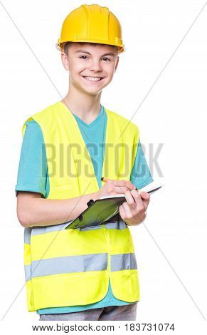 Emotional portrait of teen boy wearing safety jacket and yellow hard hat. Happy child with notebook and pen writing something, isolated on white background. Funny cute guy construction worker.