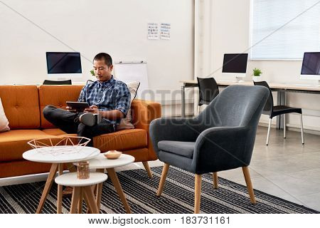 Focused young Asian designer working online with a digital table while sitting alone on a sofa in a large modern office