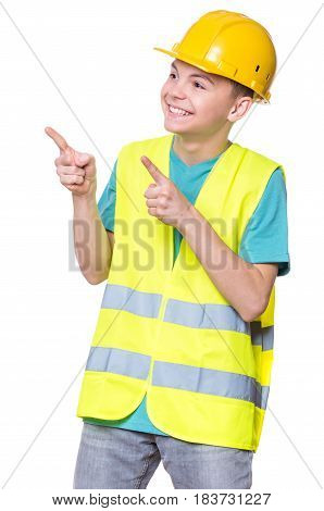 Emotional portrait of handsome caucasian teen boy wearing safety jacket and yellow hard hat. Happy child pointing and looking away, isolated on white background.