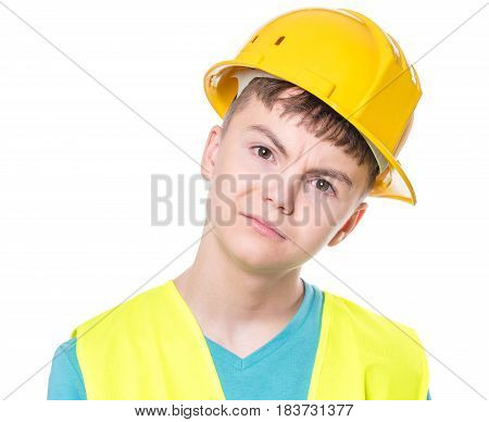 Emotional portrait of handsome caucasian teen boy wearing safety jacket and yellow hard hat. Unhappy child looking at camera, isolated on white background.