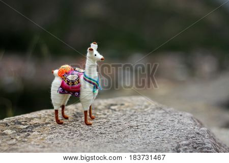 Small toy of animal alpaca standing on the hill