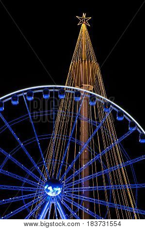 Orange and blue christmas lighting installed on tower and big wheel