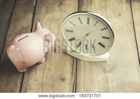 clock and piggy bank on wooden table