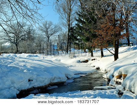 Winter rural landscape in sunny weather- winter view of rural houses with stream and winter snowdrifts on the foreground. Picturesque winter rural landscape of winter countryside