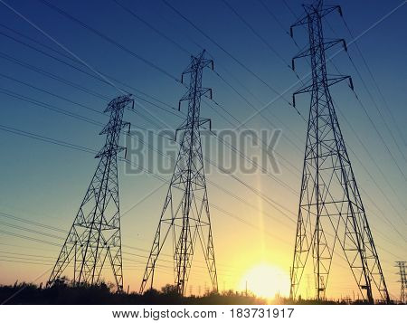 Power line poles and setting sun