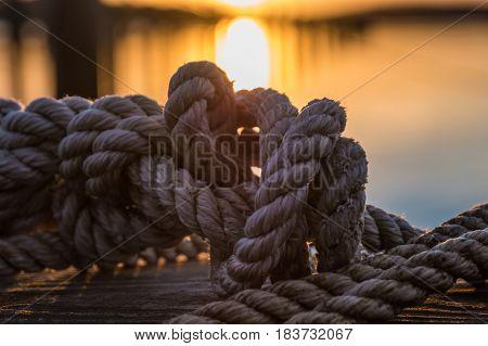 Orange and yellow sky above harbor sunset rope