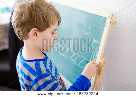Portrait of cute happy school kid boy at home making homework. Little child writing letters with chalk on board, indoors. Elementary school and education. Kid learning writing letters and numbers.