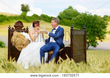 Happy wedding couple in wheat field. Beautiful bride in white dress and groom having fun on bed in hay on summer day. Just married, young family.
