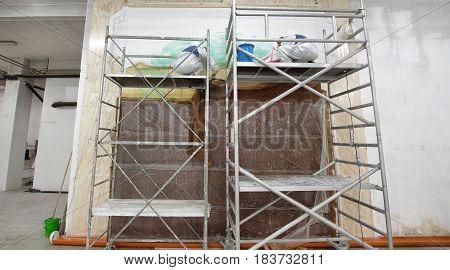 man doing a fresco treatment on scaffold