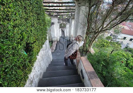 Woman on the staircase of Minerva Gardens Salerno Italy