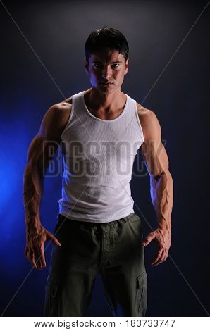 The man is flexing is muscles wearing a tank top.