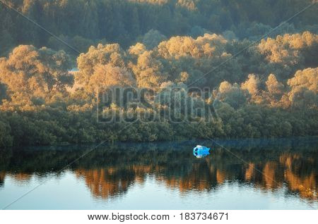 Autumn sunrise landscape-birds eye view of autumn yellowed forest and river with boat at early autumn morning. Autumn nature in sunny weather -colorul autumn water landscape with yellowed autumn trees