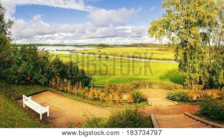 Autumn nature - valley of river Soroti Pushkinskiye Gory. Autumn colorful landscape in cloudy weather-white bench under autumn yellowed trees. Autumn landscape view of autumn October nature. Autumn background