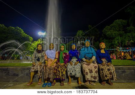 BANYUWANGI, INDONESIA: Charming park area with green vegetation and popular water fountain, people enjoying, beautiful blue evening sky in background.