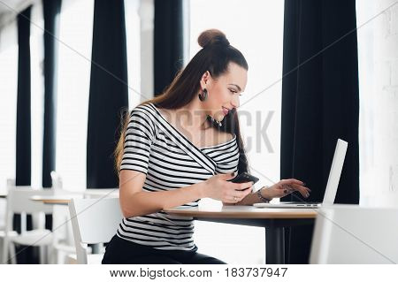 Portrait of a woman typing in a laptop while sitting at the table near window and holding phone
