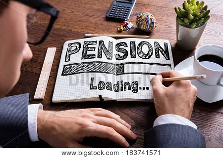 Close-up Of A Businessperson Drawing Loading Pension Concept On Notebook Over The Desk