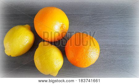 Two oranges and two lemons on the background of the gray wooden surface.