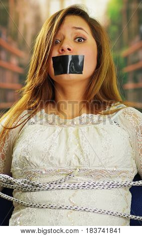 Close up portrait of scared beautiful young tied up woman being silenced with tape on her mouth concept of kidnapping