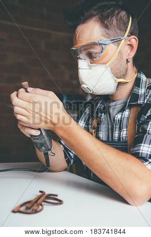 Young bearded man in safety glass and filter mask working with glasses frame.