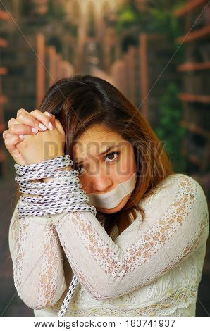 Close up portrait of beautiful young hispanic woman tied and mouth taped, concept of kidnap